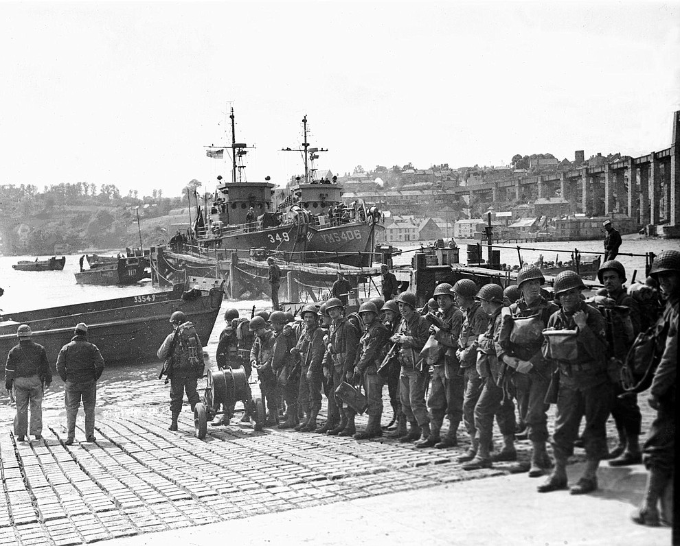 U.S. troops prepare to embark a landing craft, which will take them out to a larger ship lying off the coast, June 5, 1944, at a port in England. These soldiers are due to take part in the D-Day landings. (AP Photo/Peter J. Carroll)..