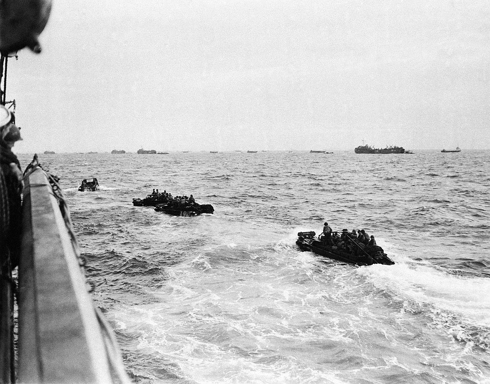 Bouncing about on the rough waters of the Channel, these landing craft loaded with assault troops head for the shore of the French coast early in the dawn of D-Day, June 6, 1944. In the surprise invasion attack, the allies suffered a minimum loss and have succeeded in cutting a 29-mile wedge in the Cherbourg Penninsular. (AP Photo)..