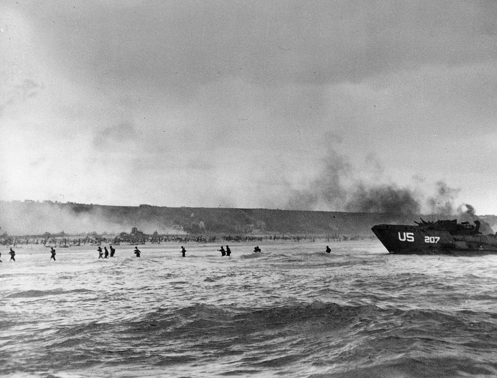 Under the cover of naval shell fire, American infantrymen wade ashore from their landing craft during the initial Normandy landing operations in France, June 6, 1944. (AP Photo/Peter Carroll)..