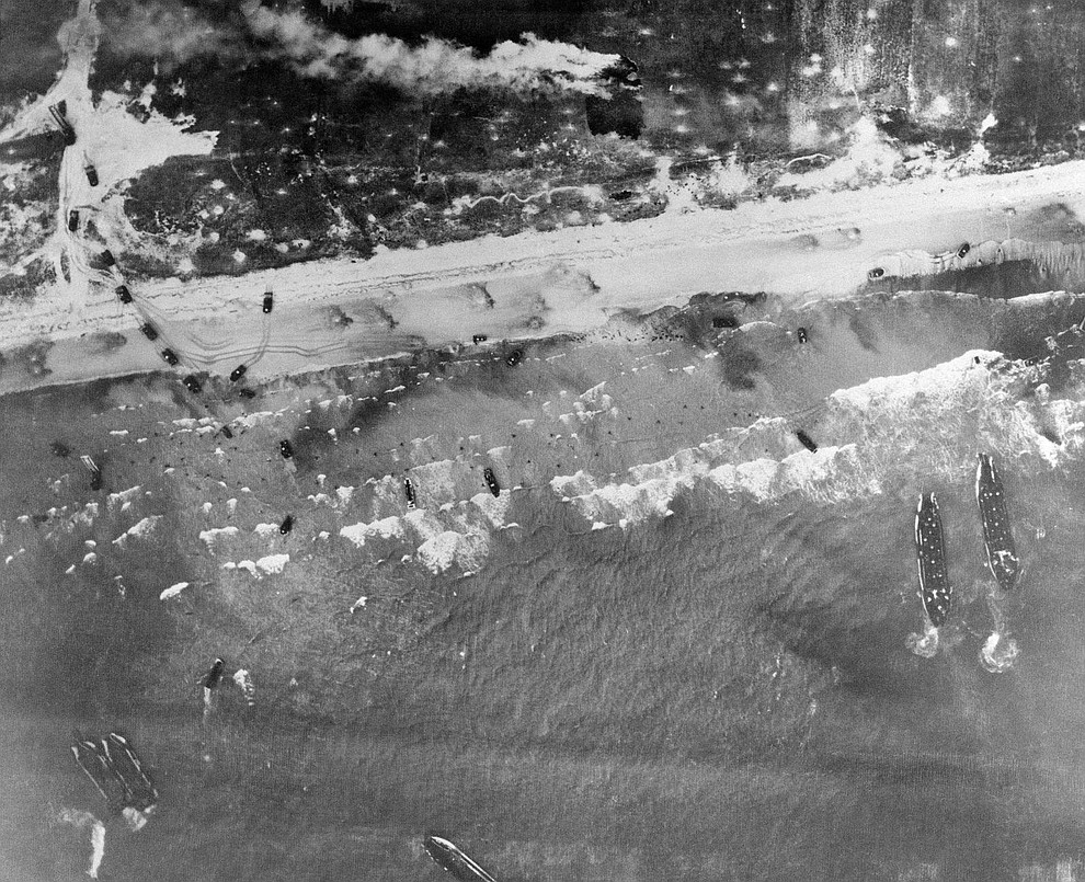 Men and assault vehicles storm the Normandy Beach of France, as allied landing craft arrive at their destination on D-Day, June 6, 1944. Note men coming ashore in surf and vehicles starting inland. (AP Photo)..
