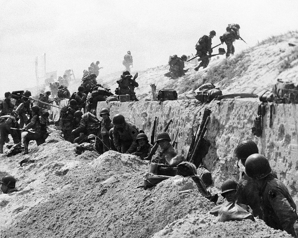 American troops move over the crest of a hill to the interior of Northern France, June 6, 1944. (AP Photo)..