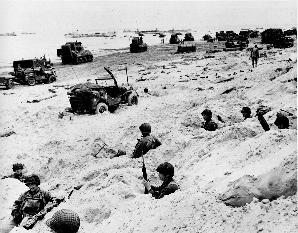 Sitting in the cover of their foxholes, American soldiers of the Allied Expeditionary Force secure a beachhead during initial landing operations at Normandy, France, June 6, 1944. In the background amphibious tanks and other equipment crowd the beach, while landing craft bring more troops and material ashore. (AP Photo/Weston Haynes)..