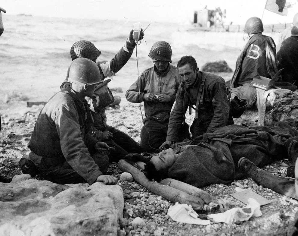 U.S. Army medical personnel administer a plasma transfusion to a wounded comrade, who survived when his landing craft went down off the coast of Normandy, France, in the early days of the Allied landing operations in June 1944. (AP Photo)..