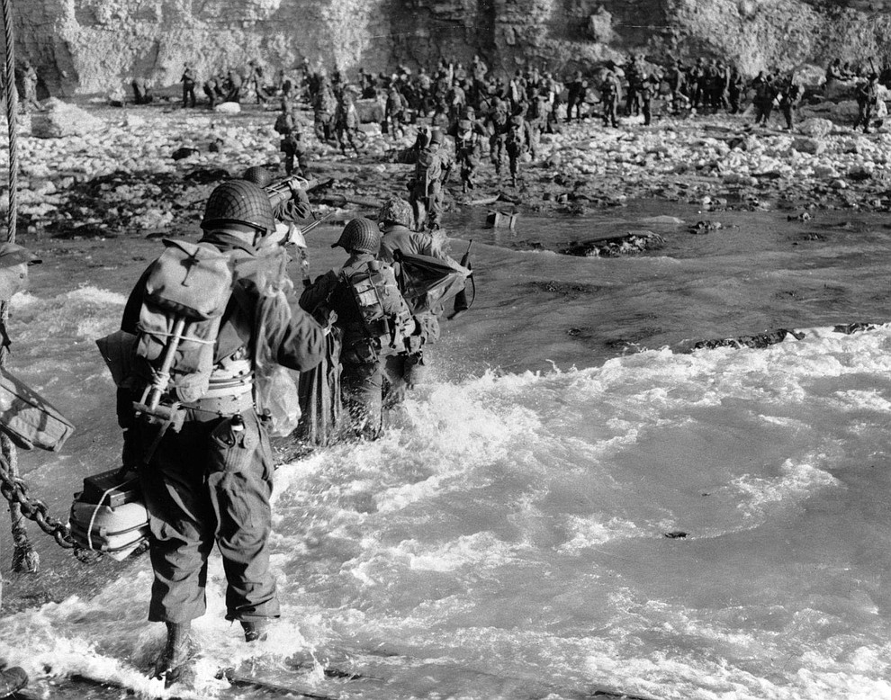 U.S. reinforcements wade through the surf as they land at Normandy in the days following the Allies' June 1944, D-Day invasion of occupied France. (AP Photo)..