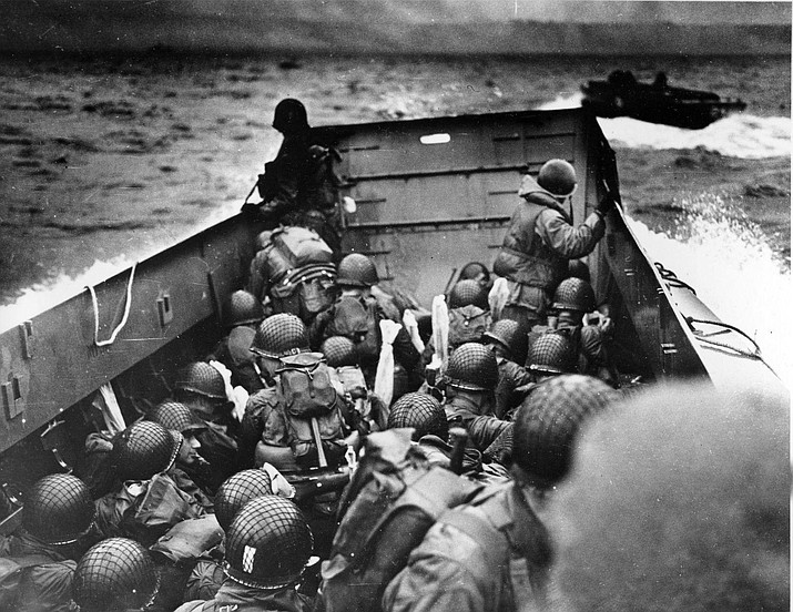 In this photo provided by the U.S. Coast Guard, a U.S. Coast Guard landing boat, tightly packed with helmeted soldiers, approaches the shore at Normandy, France, during initial Allied landing operations, June 6, 1944. These vessels, known as Higgins boats, ride back and forth across the English Channel, bringing wave after wave of reinforcement troops to the Allied beachheads. (AP Photo)