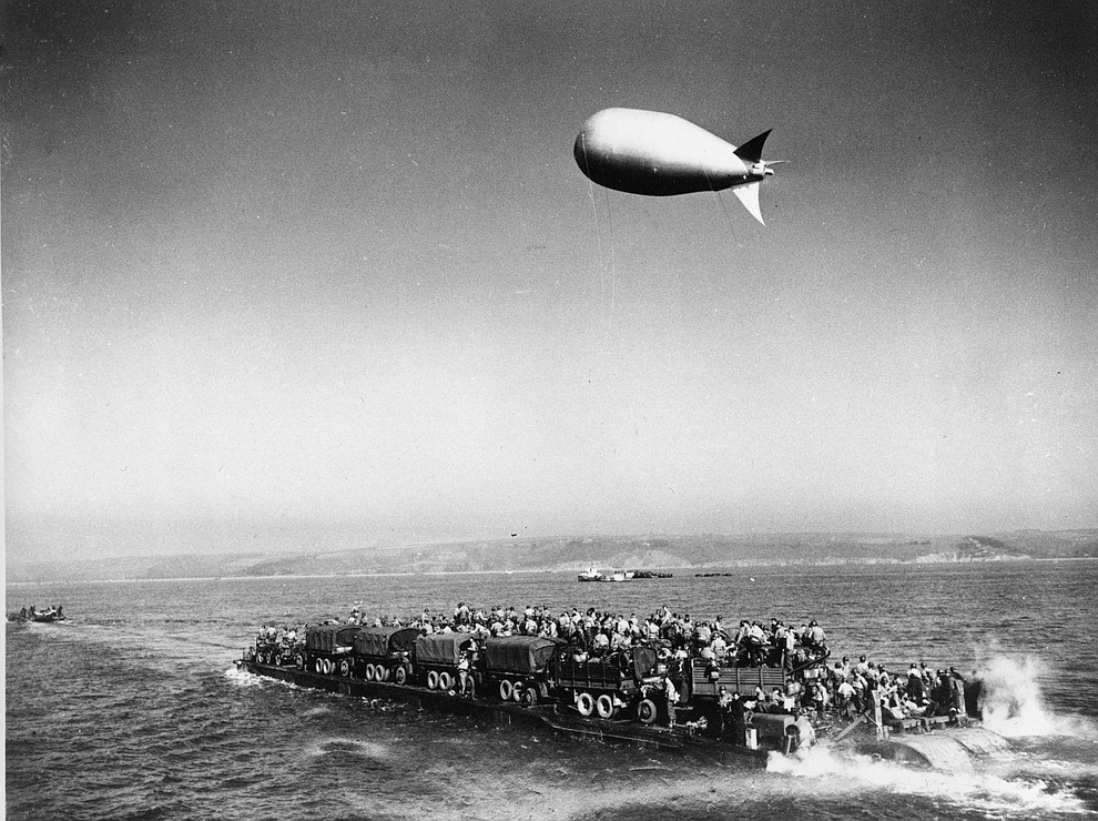 A barrage balloon cruises overhead as a heavily loaded Rhino-Ferry undergoes a test trip before it is used in the landing operations at the Normandy coast of France, in June 1944. (AP Photo)