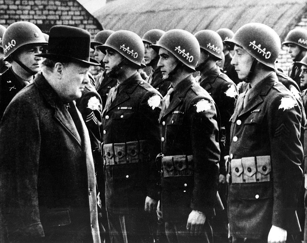 """British Prime Minister Winston Churchill, left, reviews American troops at a base in England on the eve of D-Day, June 1944, during World War II. The initials AAAO on the steel helmets with a line across the As stands for """"Anywhere, Anytime, Anyhow, Bar Nothing."""" The identification shoulder patches of the G.I.s are blotted out by the censor. (AP Photo).."""