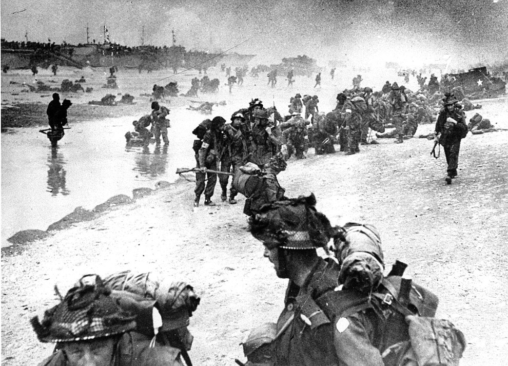 In this photo provided by the British Navy, wounded British troops from the South Lancashire and Middlesex regiments are being helped ashore at Sword Beach, June 6, 1944, during the D-Day invasion of German occupied France during World War II. (AP Photo/British Navy)..