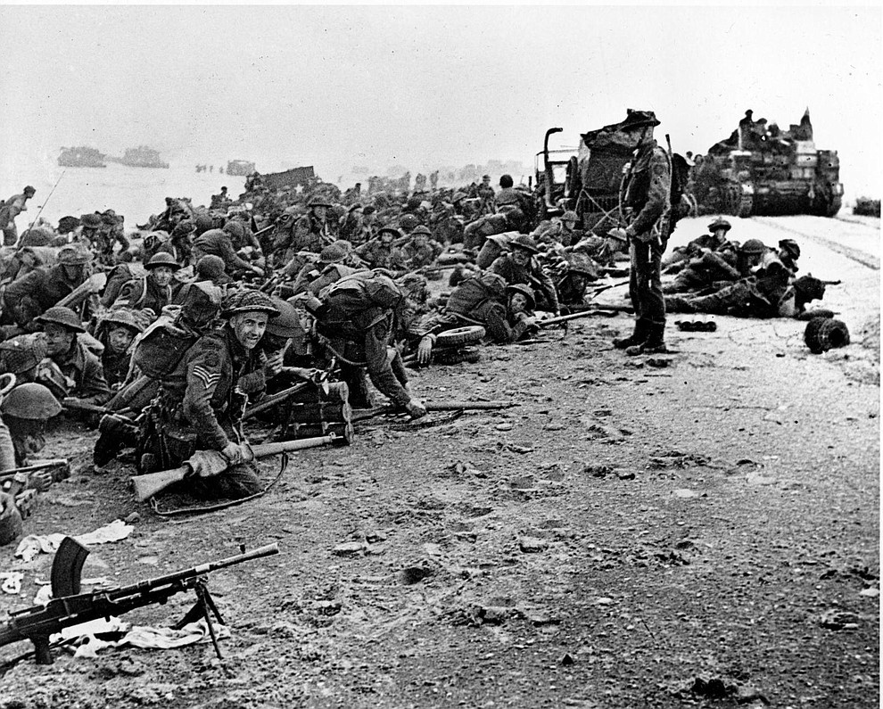 After landing at the shore, these British troops wait for the signal to move forward, during the initial Allied landing operations in Normandy, France, June 6, 1944. (AP Photo)..