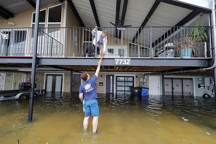 Rudy Horvath hands a piece of wood up to his wife Dawn Horvath, as their home, a boathouse in the West End section of New Orleans, takes on water a from storm surge in Lake Pontchartrain, in advance of Tropical Storm Cristobal, Sunday, June 7, 2020. (AP Photo/Gerald Herbert)
