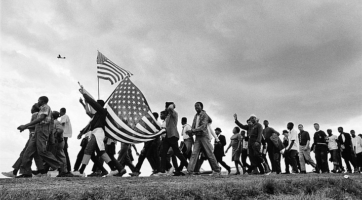 """In 1963, Matt Heron moved to Jackson, Mississippi, with his family to join the Civil Rights Movement. He organized The Southern Documentary Project — a team of eight photographers recording the rapid social change taking place in the South. Above is Heron's 1965 photo capturing the march from Selma to Montgomery, Alabama. (Photo by Matt Heron via Smithsonian """"Voices and Votes"""" exhibit)"""