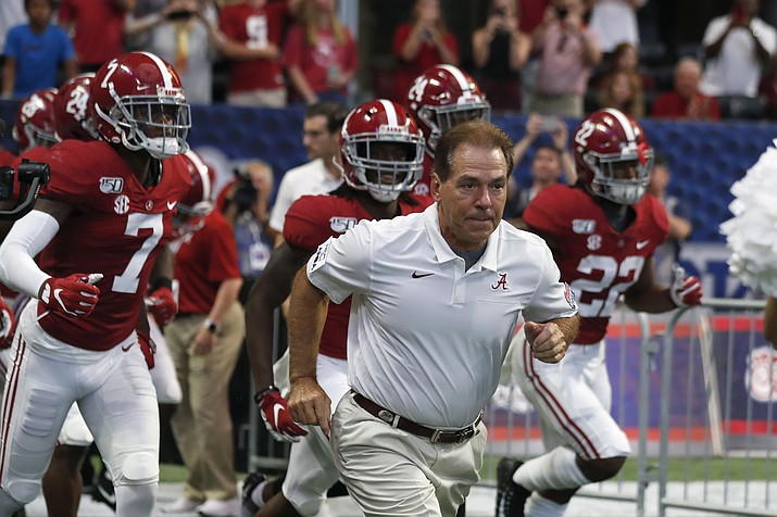In this Aug. 31, 2019, file photo, Alabama head coach Nick Saban leads his team onto the field for a an NCAA college football game against Duke, in Atlanta. Around the country schools are taking the first cautious and detailed steps toward playing football through a pandemic, attempting to build COVID-19-free bubbles around their teams as players begin voluntary workouts throughout June. Thousands of athletes will be tested for COVID-19 though not all. (John Bazemore/AP, file)