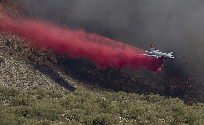 A DC-10 air tanker drops thousands of gallons of retardant at the base of the Bighorn Fire burning above La Reseve along Pusch Ridge on Saturday, June 6 in Coronado National Forest north of Tucson, Ariz. Arizona's wildfire season is already in high gear, thanks in large part to human carelessness but also weather conditions last winter that produced an abundance of vegetation now serving as fuel for fires. (Rick WileyArizona Daily Star via AP)