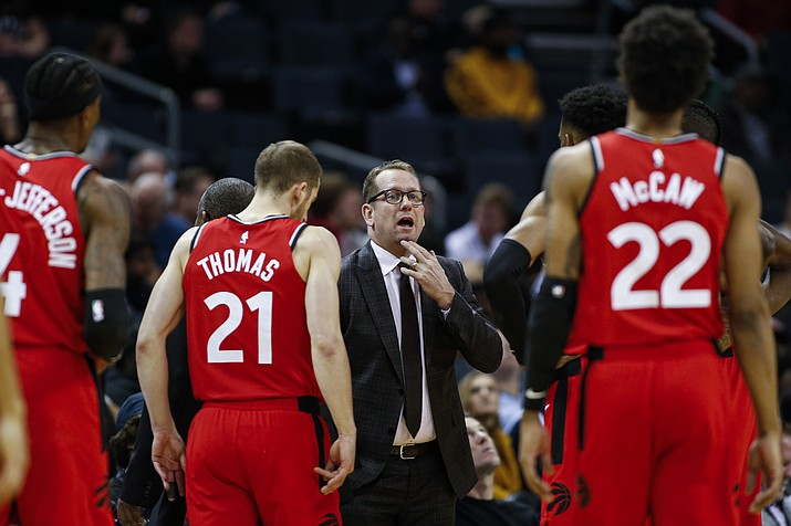 In this Jan. 8, 2020 photo, Toronto Raptors coach Nick Nurse, center, gathers his team during a timeout in the first half of an NBA basketball game against the Charlotte Hornets in Charlotte, N.C. The Raptors have an NBA championship to defend, a very long stay at the Disney complex awaiting them and plenty of unanswered questions on how the restart of the season will work. (Nell Redmond/AP, File)