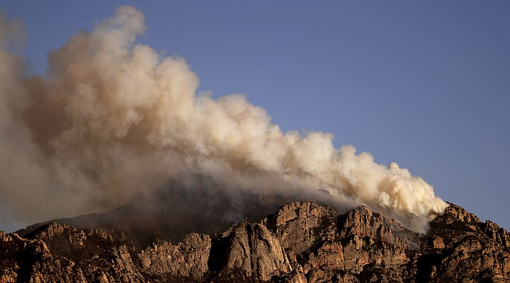 A stiff wind out of the southwest pushes the Bighorn Fire into the central Santa Catalina Mountains as seen from Oro Valley, Ariz., Saturday, June 13, 2020. The fire has grown and is now threatening Mt. Lemmon and the town of Summerhaven, Ariz. (Kelly Presnell/Arizona Daily Star via AP)