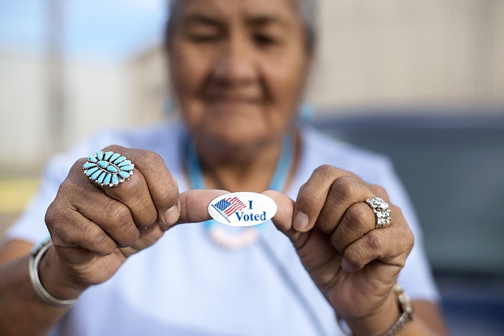 """Mildred James of Sanders, Arizona, shows off her """"I Voted"""" sticker as she waits for results of the Navajo Nation presidential primary election to be revealed in Window Rock, Ariz. In race for Navajo Nation president, candidates have similar priorities. Their leadership style might be the deciding factor. The contenders are Joe Shirley Jr., and Jonathan Nez. (AP Photo/Cayla Nimmo, File)"""