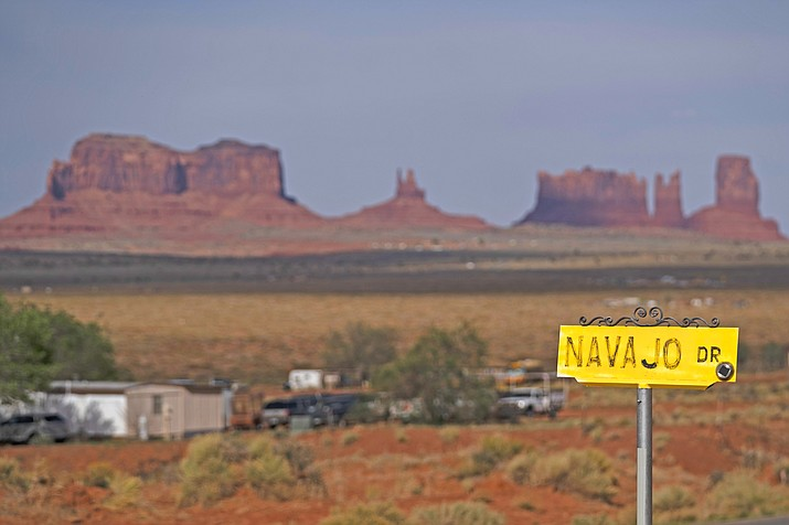 A sign marks Navajo Drive as Sentinel Mesa, homes and other structures in Oljato-Monument Valley, Utah on the Navajo Reservation, stand in the distance. Even before the pandemic, people living in rural communities and on reservations were among the toughest groups to count in the 2020 census. (AP Photo/Carolyn Kaster)