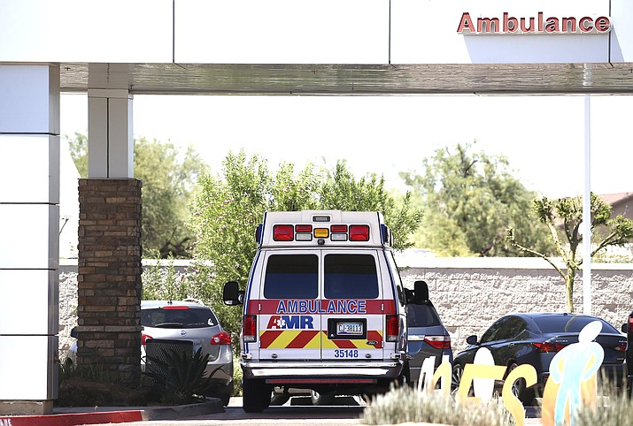 An ambulance is parked at Arizona General Hospital June 10, in Laveen, Arizona, as Arizona hospitals that are expected to be able to treat new cases of coronavirus without going into crisis mode were above 80 percent capacity June 16, a milestone that should trigger an automatic stop to elective surgeries at affected hospitals. The state is dealing with a surge in virus cases and hospitalizations that experts say is likely tied to Gov. Doug Ducey's ending of statewide closure orders in mid-May. (AP Photo/Ross D. Franklin)
