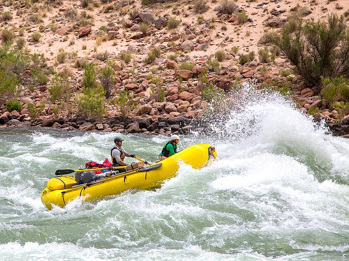 An inflatable raft running a whitewater rapid and entering a large wave on the Colorado River is thrown into the air. (NPS/Neal Herbert)