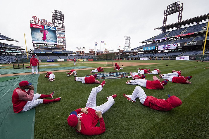 In this April 7, 2017 photo, members of the Philadelphia Phillies stretch before the team's baseball game against the Washington Nationals in Philadelphia. Five players for the Philadelphia Phillies have tested positive for COVID-19 at the team's spring camp in Florida, prompting the club to indefinitely close the complex.The team also said Friday, June 19, 2020, that three staff members at the camp have tested positive. The club didn't identify any of those affected. (Matt Rourke/AP, File)