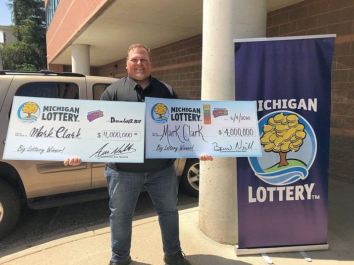 Mark Clark of South Rockwood, Michigan, holds his two $4 million winning scratch-off lottery tickets. (Michigan Lottery)