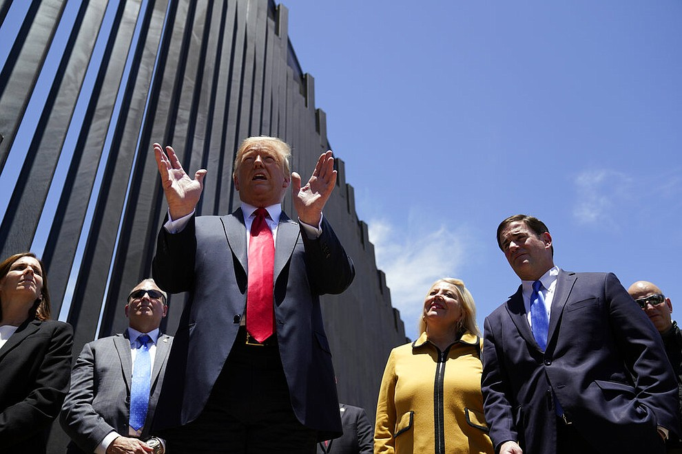 President Donald Trump speaks as he tours a section of the border wall, Tuesday, June 23, 2020, in San Luis, Ariz. Arizona Gov. Doug Ducey, second from right, and Rep. Debbie Lesko, R-Ariz., third from right. (AP Photo/Evan Vucci)