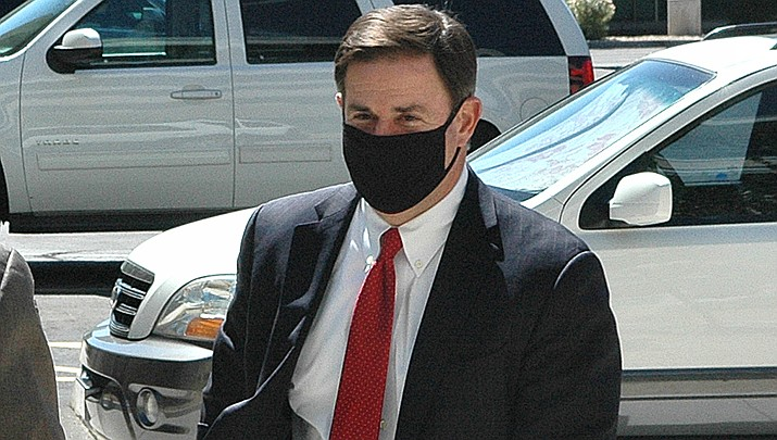 Arizona Gov. Doug Ducey is shown wearing a mask in public last week, a recent development for the governor. Ducey wore an Arizona flag mask during a visit by U.S. President Donald Trump on Tuesday, June 23. (File photo by Howard Fischer/For the Miner)