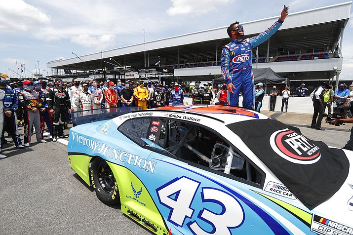 In this June 22, 2020, file photo, Bubba Wallace takes a selfie of himself and of other drivers who had pushed his car to the front in the pits at Talladega Superspeedway before the NASCAR Cup Series auto race in Talladega Ala., Monday June 22, 2020. The noose found hanging in Wallace's garage stall at Talladega had been there since at least last October, federal authorities said Tuesday, June 23, in announcing there will be no charges filed in an incident that rocked NASCAR and its only fulltime Black driver. (AP Photo/John Bazemore, File)