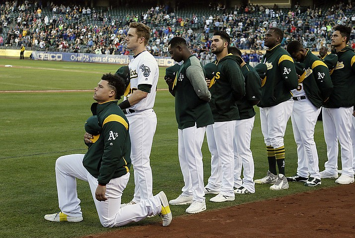 In this Sept. 23, 2017, file photo, Oakland Athletics catcher Bruce Maxwell kneels during the national anthem before the team's baseball game against the Texas Rangers in Oakland, Calif. Baseball is scheduled to return July 23 or 24 with a skewed, 60-game schedule, rather than the full plate of 162. A shortened, contorted season ordered by Commissioner Rob Manfred on Tuesday night after owners and players couldn't come to a new economic agreement against the backdrop of the virus outbreak. (Eric Risberg, AP File)