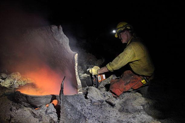 A McCall smoke jumper uses a saw on a night-shift of the Mangum Fire. (Photo/Mike McMillan/USFS)