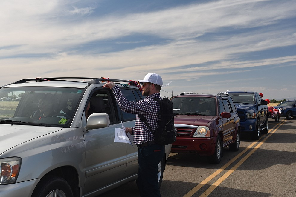 Bradshaw Mountain Highschool Teacher Jack Fields greets carloads of graduating seniors in the parking lot of Findlay Toyota Center in Prescott Valley on Wednesday, June 24 2020, prior to the graduation parade ceremony. (Jesse Bertel/Courier).