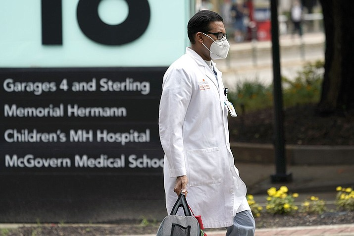 A health care professional walks through the Texas Medical Center Thursday, June 25, 2020, in Houston. The leaders of several Houston hospitals said they were opening new beds to accommodate an expected influx of patients with COVID-19, as coronavirus cases surge in the city and across the South. (David J. Phillip/AP)