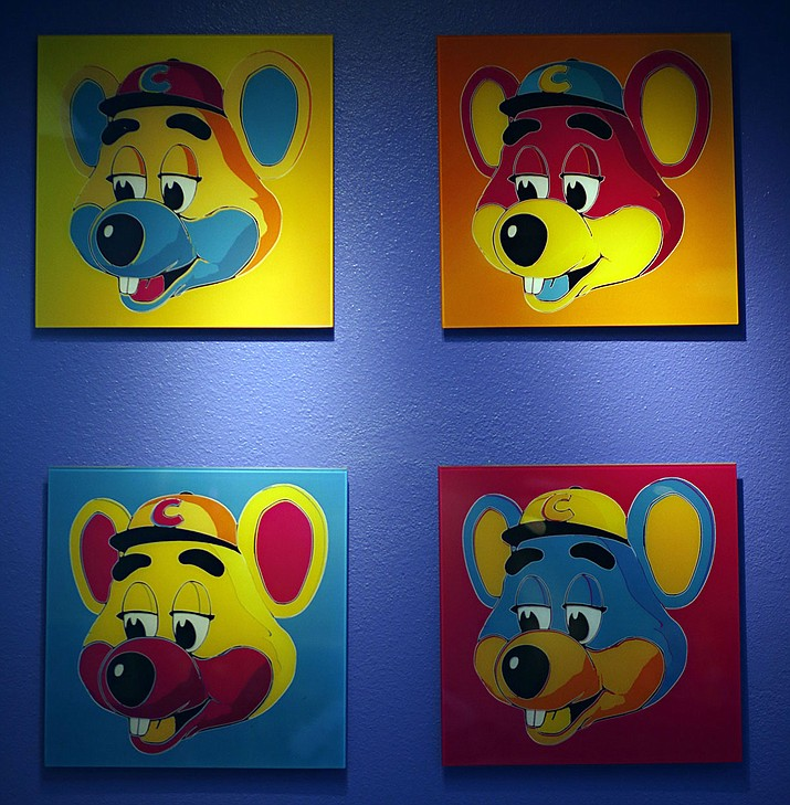 """This Jan. 16, 2014 file photo shows paintings hanging on a wall at Chuck E. Cheese's in Dallas. Chuck E. Cheese pizzeria, that Mecca of fun for children but the bane of many parents, is filing for bankruptcy protection. CEC Entertainment Inc. said Thursday, Jan. 25, 2020, it was filing for voluntary protection under Chapter 11 """"in order to overcome the financial strain resulting from prolonged, COVID-19 related venue closures."""" (G.J. McCarthy/The Dallas Morning News via AP)"""
