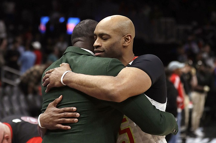 Atlanta Hawks guard Vince Carter, right, hugs former Hawk Dominique Wilkins as he leaves the court following an NBA basketball game against the New York Knicks Wednesday, March 11, 2020, in Atlanta. (John Bazemore/AP)