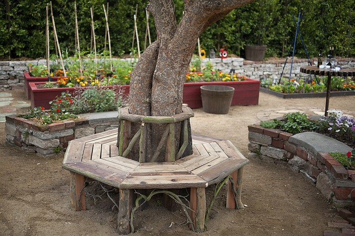 In this 2011 photo provided Martha Benedict, a bench around a tree and raised flower and vegetable beds, all built by landscape designer Katharine Pinney from discarded scaffolding, are shown in a kitchen garden at a home in La Canada, Calif. Homeowners can transform an ordinary looking landscape with some imagination, design, and perhaps the help of a local agriculture extension service, landscape professional or private nursery. (Martha Benedict/Katharine Pinney via AP)