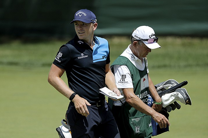 Matt Wallace, left, of England, walks with his caddie David McNeilly to the fourth tee box during the second round of the Travelers Championship golf tournament at TPC River Highlands, Friday, June 26, 2020, in Cromwell, Conn. Wallace is playing the second round by himself after two other golfers in his group, Denny McCarthy and Bud Cauley, withdrew from the tournament. McCarthy told Golfchannel.com that he withdrew from the tournament after feeling sick Thursday night and testing positive for the coronavirus on Friday. Cauley, who played with McCarthy on Thursday, also withdrew before Friday's second round. McCarthy became the third PGA Tour player to test positive for the virus since its restart and the second this week, joining Cameron Champ who withdrew on Tuesday. Nick Watney withdrew just before the second round of last week's RBC Heritage Championship. (Frank Franklin II/AP)