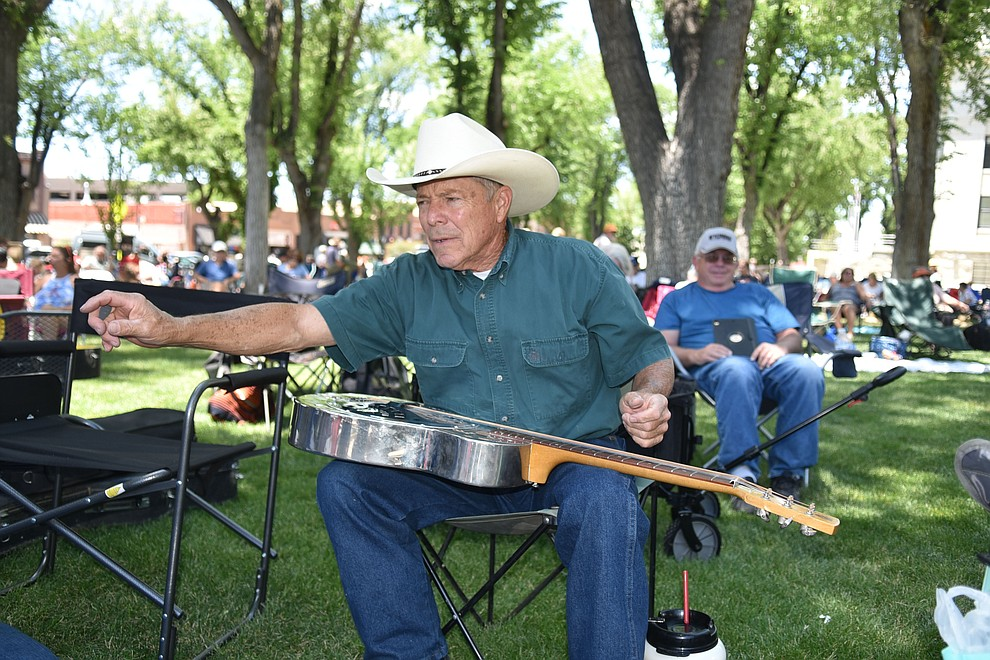 Mike Weatherford, 72, plays his guitars while watching Quick Sand Soup perfom at the Prescott Bluegrass Festival at the Yavapai County Courthouse on Saturday afternoon, June 27, 2020. (Jesse Bertel/Courier)