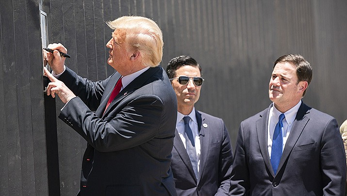 U.S. President Donald Trump signs a plaque on a new section of border wall during a visit to the U.S.-Mexico border near Yuma on Tuesday, June 23. Arizona Gov. Doug Ducey, right, looks on. (Official White House photo/Public domain)