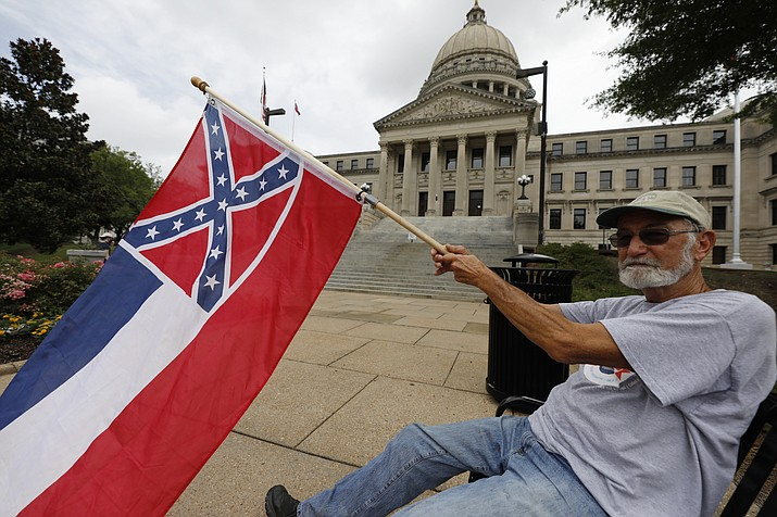 Larry Eubanks of Star waves the current Mississippi state flag as he sits before the front of the Capitol, Saturday, June 27, 2020, in Jackson, Miss. While a supporter of the current flag, Eubanks says he would hope lawmakers would allow a proposed flag change to be decided by the registered voters. The current state flag has in the canton portion of the banner the design of the Civil War-era Confederate battle flag, that has been the center of a long-simmering debate about its removal or replacement. (Rogelio V. Solis/AP)