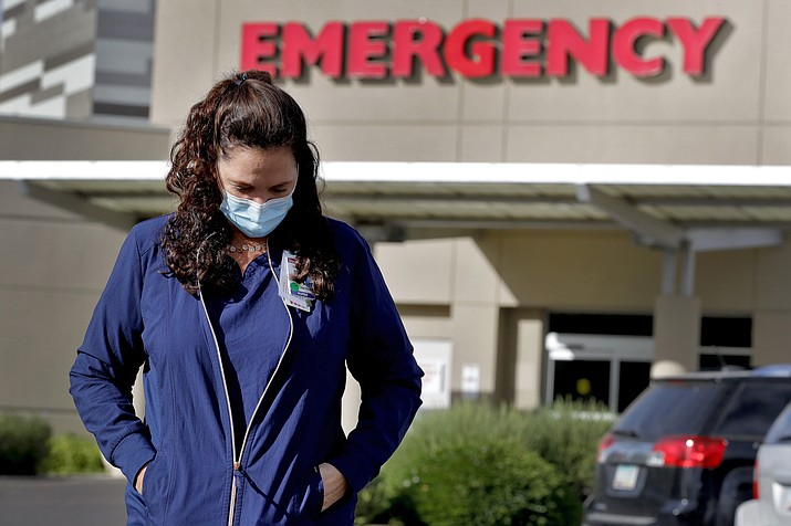 Caroline Maloney stands outside Honor Health's Scottsdale Osborn Medical Center at the end of her overnight shift early Friday, June 26, 2020 in Scottsdale, Ariz. Arizona nurses and doctors find themselves on the frontline as the coronavirus rips through the state, making it one of the world's hot spots. (Matt York/AP)