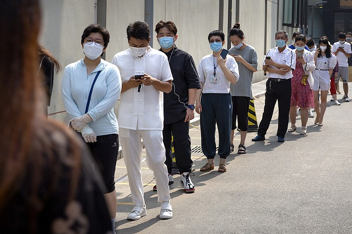 People wearing face masks stand in line for coronavirus tests at a community health clinic in Beijing, Sunday, June 28, 2020. China reported more than a dozen of new confirmed cases of COVID-19 on Sunday, all but a few of them from domestic transmission in Beijing, which has seen a recent spike in coronavirus infections. But authorities in the Chinese capital say a campaign to conduct tests on employees at hair and beauty salons across the city has found no positive cases so far, in a further sign that the recent outbreak has been largely brought under control. (Mark Schiefelbein/AP)