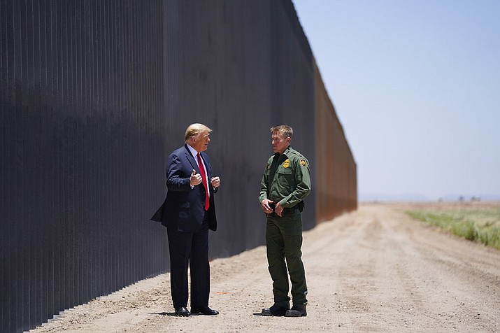 President Donald Trump speaks with Rodney Scott, the U.S. Border Patrol Chief, as he tours a section of the border wall, Tuesday, June 23, 2020, in San Luis, Ariz.  A federal appeals court has ruled the Trump administration illegally diverted $2.5 billion in military construction funds to finance his border wall through Arizona, California and New Mexico. (Evan Vucci/AP)