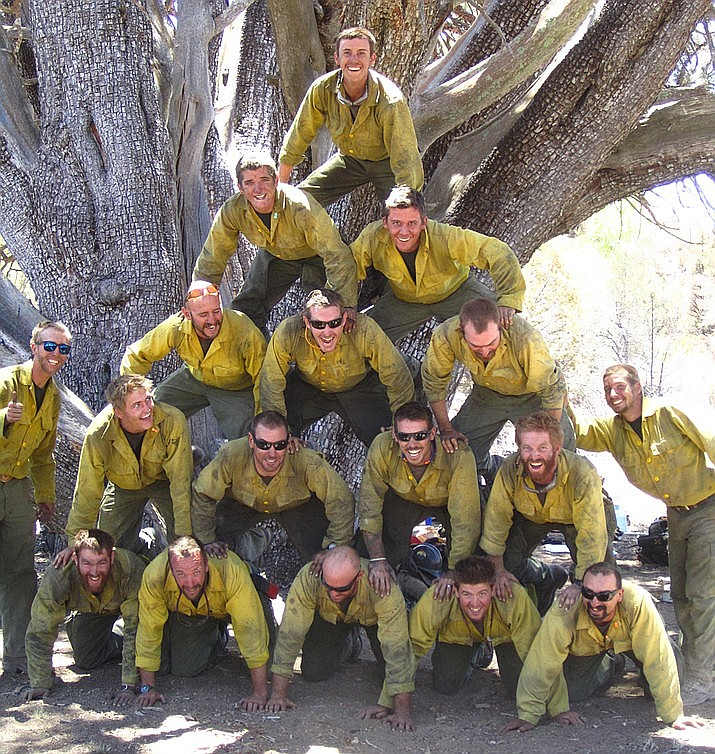 The Granite Mountain Hotshots form a pyramid in front of an ancient alligator juniper tree atop Granite Mountain during the Doce Fire of June 2013. The Hotshots saved the juniper as well as communities below the mountain during the Doce Fire. (Courier file photo)