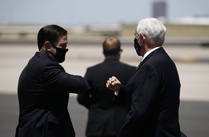 Vice President Mike Pence, right, is greeted with an elbow bump by Arizona Gov. Doug Ducey, left, as he arrives to discuss the surge in coronavirus cases Wednesday, July 1, 2020, in Phoenix. (Ross D. Franklin/AP)