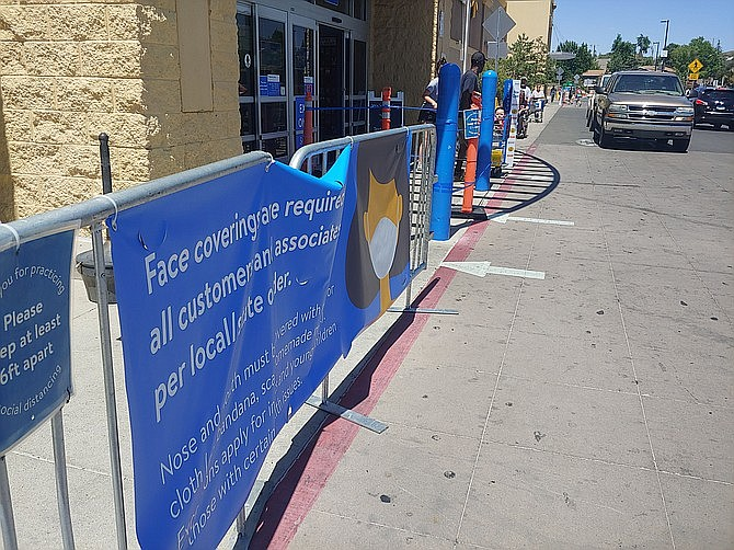 The Walmart on Gail Gardner Way in Prescott, as seen on June 30, 2020, has a blue banner hanging on fencing at the entrance to the store telling customers that it is requiring them to wear face coverings per a state/local mandate related to the COVID-19 pandemic. (Doug Cook/Courier)