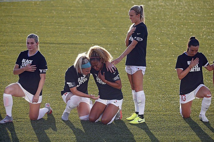 In this June 27, 2020, file photo, Chicago Red Stars' Julie Ertz, second from left, holds Casey Short, center, while other players for the team kneel during the national anthem before an NWSL Challenge Cup soccer match against the Washington Spirit at Zions Bank Stadium in Herriman, Utah. The National Women's Soccer League revised its anthem policy after most players knelt during the anthem before season-opening games last weekend at the Challenge Cup. (Rick Bowmer/AP file)