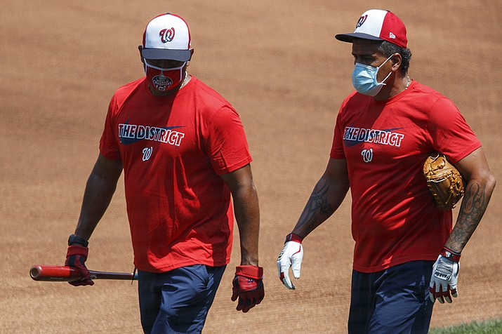Washington Nationals' manager Dave Martinez, left, and bullpen coach Henry Blanco walk together during a baseball training camp workout at Nationals Stadium, Sunday, July 5, 2020, in Washington. Baseball's two World Series teams canceled workouts Monday because of COVID-19 testing delays that one executive worried could endanger the baseball season. (Carolyn Kaster/AP)