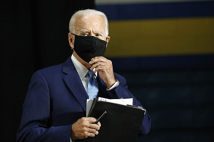 Democratic presidential candidate, former Vice President Joe Biden puts on a face mask to protect against the spread of the new coronavirus as he departs after speaking at Alexis Dupont High School in Wilmington, Del., Tuesday, June 30, 2020. (Patrick Semansky/AP)