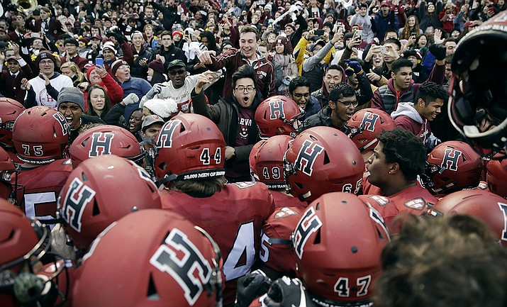 In this Nov. 17, 2018, file photo, Harvard players, students and fans celebrate their 45-27 win over Yale after an NCAA college football game at Fenway Park in Boston. Harvard defeated Yale. The Ivy League has canceled all fall sports because of the coronavirus pandemic. (Charles Krupa, AP file)