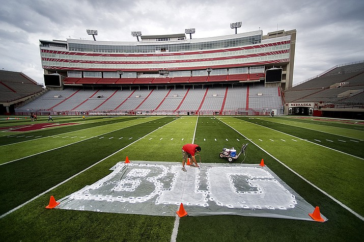 In this Thursday, Oct. 6, 2011 file photo, Turf manager Jared Hertzel touches up the newly-painted Big Ten conference logo on the football field at Memorial Stadium in Lincoln, Neb. The Big Ten Conference announced Thursday, July 9, 2020 it will not play nonconference games in football or several other sports this fall because of the coronavirus pandemic. (Jacob Hannah/Lincoln Journal Star via AP)